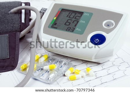 blood pressure monitor, tablets and ECG - stock photo