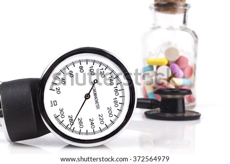 Blood pressure sphygmomanometer close-up with stethoscope and pills in the background - stock photo