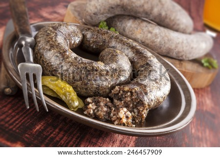Blood sausage and rice sausage on wooden background. Culinary traditional european eating, rustic style. - stock photo