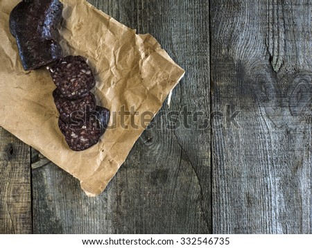 Blood sausage on crumpled wrapping paper on an old wooden table - stock photo