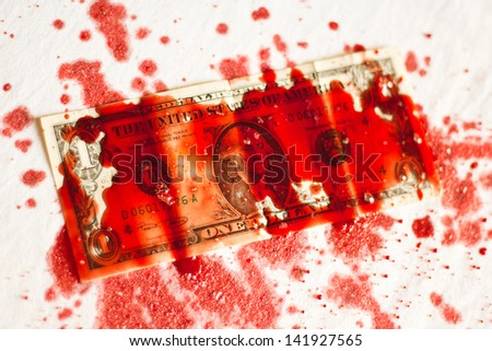 blood splatter on dollar bill on white fabric background - stock photo
