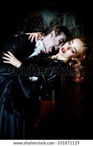 Bloodthirsty male vampire in medieval dress is biting a beautiful lady. Halloween.  - stock photo