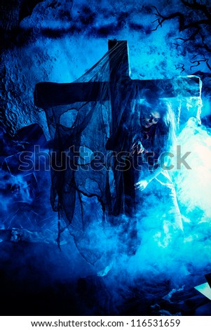 Bloodthirsty zombi standing at the night cemetery in the mist and moonlight. - stock photo