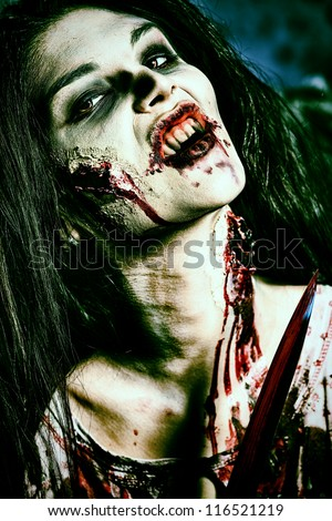 Bloodthirsty zombi with a knife standing at the night cemetery in the mist and moonlight. - stock photo
