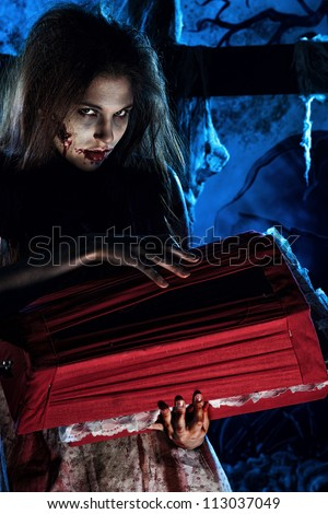 Bloodthirsty zombie standing at the night cemetery in the mist and moonlight. - stock photo