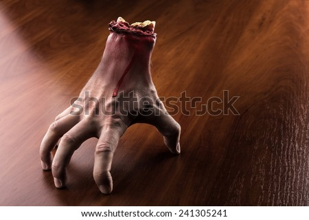 Bloody arm stands on the table - stock photo