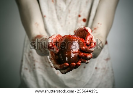 Bloody Halloween theme: crazy killer keeps bloody hands torn bloody human heart and experiencing depression and pain - stock photo