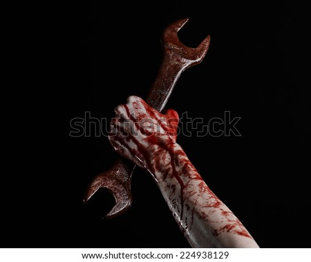 bloody hand holding a big wrench, bloody wrench, big key, bloody theme, halloween theme, crazy mechanic, murderer, psycho, violence, zombies, black background, isolated, revolution