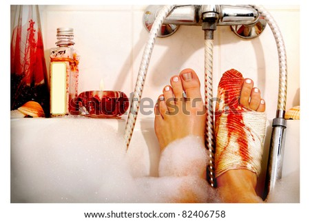 Bloody injured feet in a romantic bath with foam - stock photo