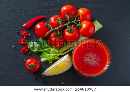 Bloody Mary cocktail ingredients - cocktail cherry tomatoes, celery, chili, lemon, on dark stone background, top view - stock photo