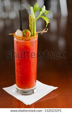 bloody mary cocktail isolated on a busy bar top garnished with onions, olives, asparagus and celery - stock photo