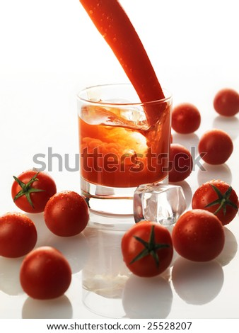 bloody mary cocktail with splash of juice and tomatoes around of it - stock photo