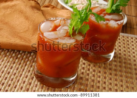 Bloody Mary cocktails or vegetable juice on a bamboo counter - stock photo