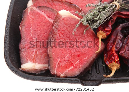 bloody raw beef meat on bbq pan with pepper and thyme isolated on white background