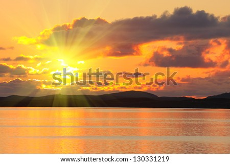 bloody sunset over the sea and mountains peaks - stock photo