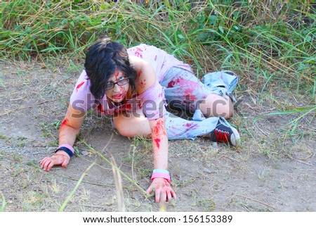 Bloody woman with a ripped shirt wonders in a field - stock photo