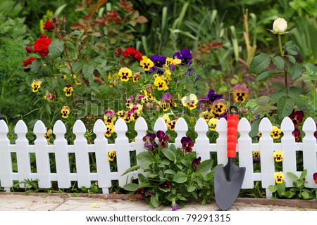 Blooming Fence of Flowers. A small flower bed near the house - stock photo