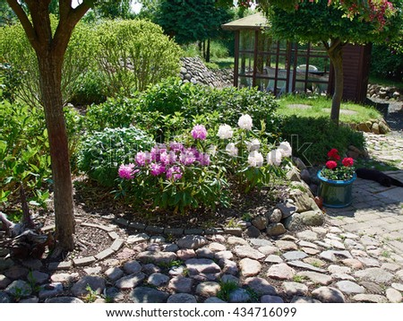 Blooming flowers and plants corner island in a beautiful garden - stock photo