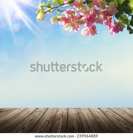 Blooming flowers and spring bokeh light background with wooden table - stock photo