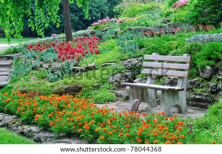 Blooming flowers, decorative plants and bushes in a summer park with bench and marigolds in front - stock photo