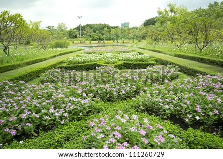 blooming flowers in a park with a pond, Flowerbed - stock photo