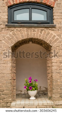 Blooming flowers in a vase in the portal brick-stone wall of a medieval castle. Mir, Belarus. - stock photo