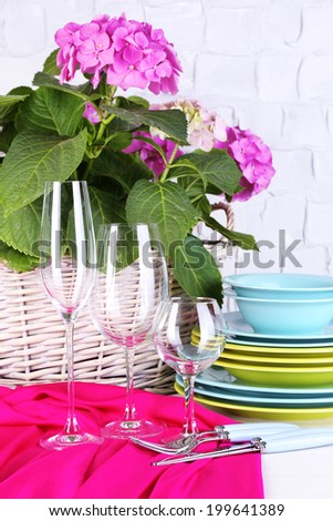 Blooming hydrangea and utensils on table on grey wall background - stock photo