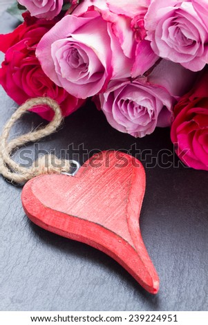 blooming  pink roses  laying  on black  stone  table with red heart - stock photo