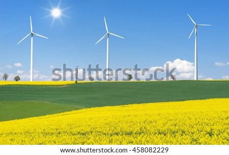 Blooming rapeseed fields with three wind turbines in hilly rural landscape in sunlight  - stock photo