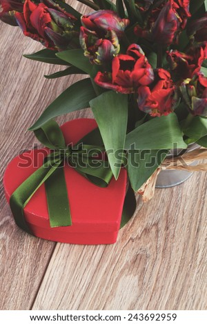 blooming  red  tulips  with heart gift box  on   table, instagram retro filter - stock photo