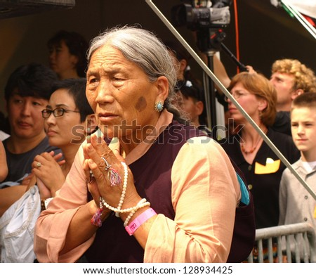 BLOOMINGTON, IND - JULY 9 : Unidentified Tibetan woman prays for world at event featuring Dali Lama and Muhammad Ali meeting for the first time in Bloomington, Ind on July 9, 2003.