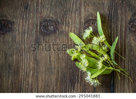 Blossoms of linden tree on wooden background. Selective focus