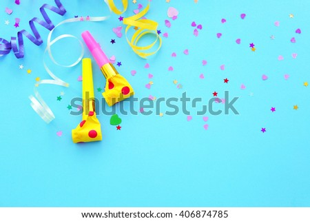Blowers, streamers and confetti on blue background - stock photo