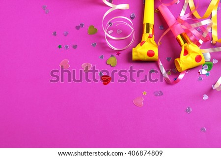 Blowers, streamers and confetti on purple background - stock photo