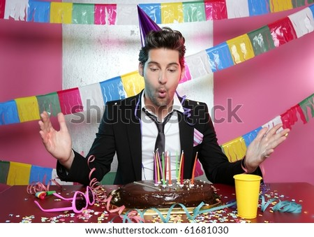Blowing a holiday party chocolate cake young handsome suit man - stock photo