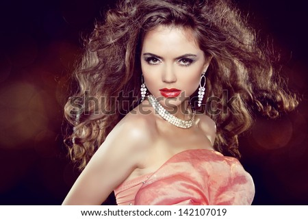 Blowing Hair. Sexy woman portrait with long brown wavy hair and make up. Jewelry and Fashion Photo - stock photo