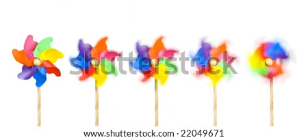 Blowing in the Wind: five toy windmills spinning stationary to fast; isolated on extendable white ground to give good copy-space; high resolution so each image can be used on its own - stock photo