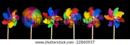 Blowing in the Wind: toy windmills; isolated on easily-extendable black ground to give good copy-space; high resolution so each image can be used on its own - stock photo