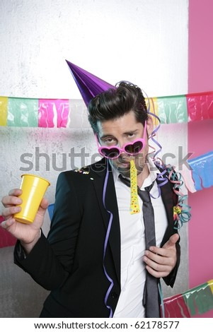 Blowing noisemaker suit party funny gesture young man - stock photo