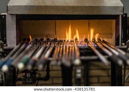 Blowing Pipes Kept Warm in the Propane Oven over Flames - stock photo
