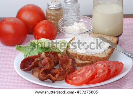BLT ingredients on white plate with glass of cold milk on pink gingham place mat.