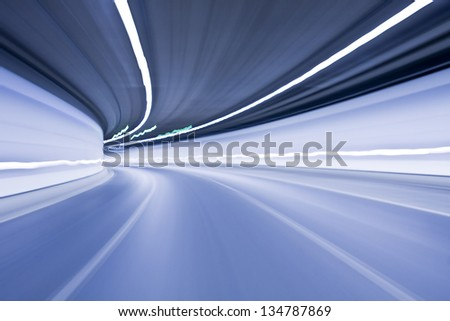 Blue Abstract blurred speed motion in urban highway road tunnel, moving toward the light
