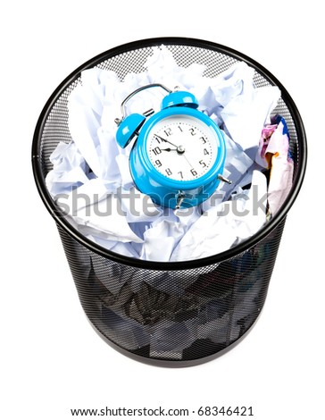 Blue alarm clock sat in a waster paper basket - stock photo