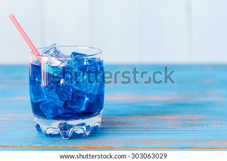 Blue alcohol or alcohol-free cocktail with straw and ice cubes on a wooden table. Empty space for text. - stock photo