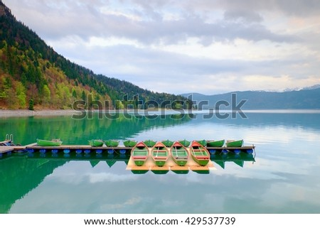 Blue Alps lake with Rental rowing boats in marina. Wharf for trip ships.