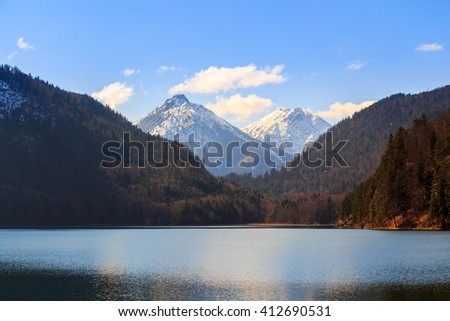 Blue Alpsee Lake in the Green Forest and Beautiful Alps Mountains. Fussen, Bavaria, Germany - stock photo