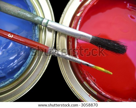 Blue an red paint cans with two brushes on top. - stock photo