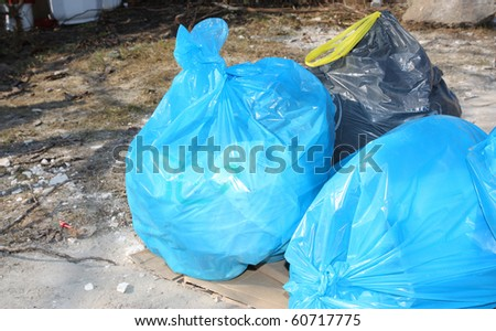 blue and black garbage bags on outdoor - stock photo