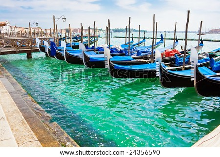 Blue and black gondola boats moored in Venice