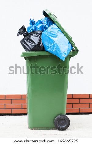 Blue and black rubbish sucks in a green litter bin - stock photo